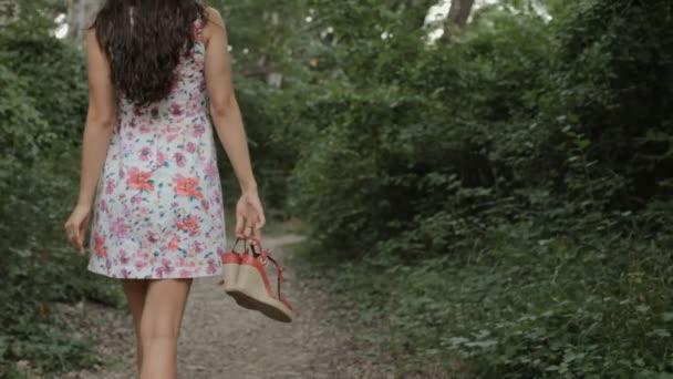 Brunetka v šatech chodí naboso na cestě v lese a kolem sebe