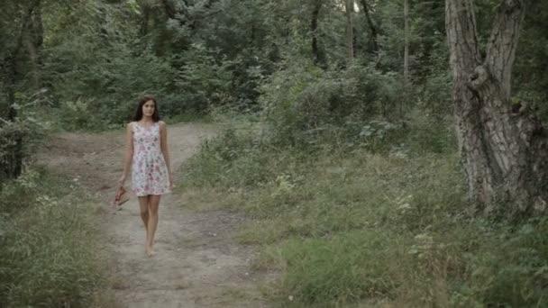 Krásná dívka v šatech, pěší podél cesty v lese