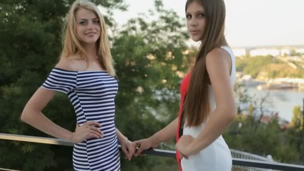 Atraktivní modely v šatech pózuje na venkovní terase