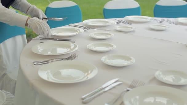Číšník opatrně položí příbory na kulatý stůl s bílým ubrusem pro banket