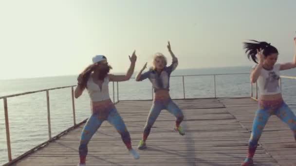 Energický twerk módní teen dívky na dřevěném molu u moře