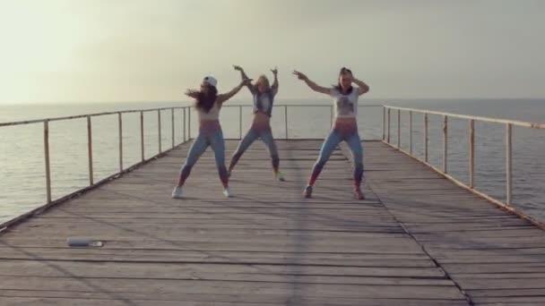 Dívky ve světlé legíny profesionálně tančí tanec na dřevěném molu u moře při západu slunce