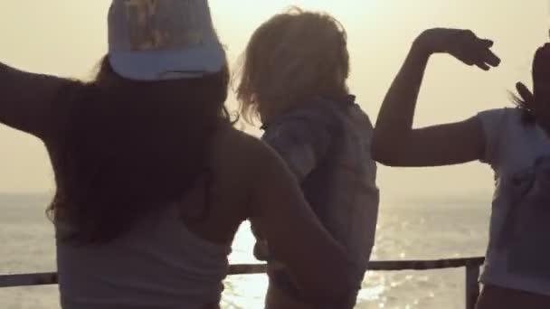 Tři veselá dívky oblečené v téže punčocháče tanec při západu slunce blízko moře