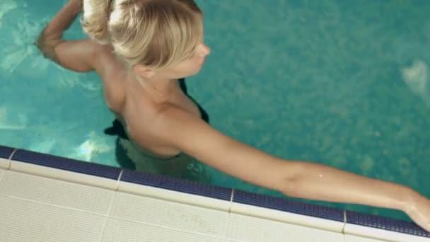Okouzlující dívka v černých bikinách relaxaci v bazénu
