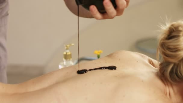 Masér proudí horká čokoláda na tělo dívky