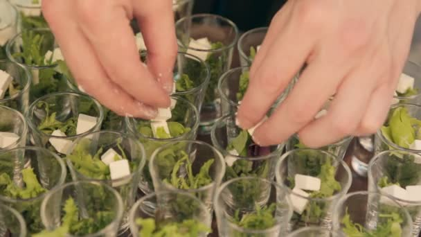 Cook adds cubes of feta cheese in containers with lettuce on the catering