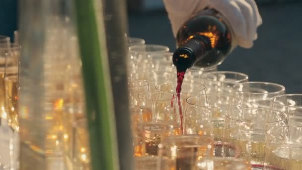Číšník nalil červené víno do sklenic na stravování