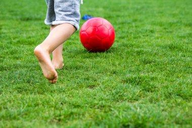 Little boy playing football on green grass