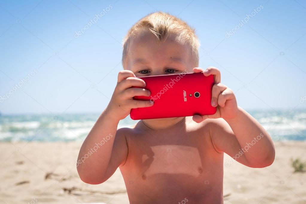 Cute boy laughing while playing with smart phone at beach near the sea