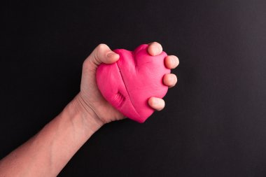 Mens hand squeezing pink heart on a black background