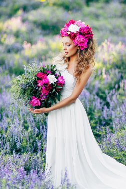 Fashion Beauty Model Girl with flowers in the hair in a wedding dress.
