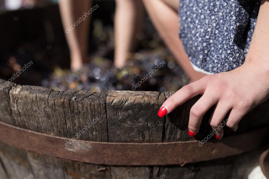 Grape stomping with girl's hand