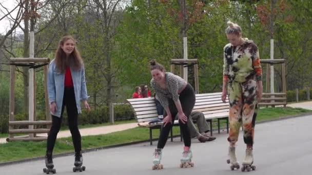 Praha, Česká republika. 04-16-2021. Tři ženy s kolečkovými bruslemi tančí a baví se v parku Stromovka v Praze na jaře.
