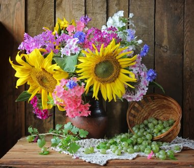 Still life with a bouquet of sunflowers and phloxes. Flowers and berries.