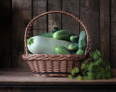 Basket with cucumbers and a vegetable marrow.