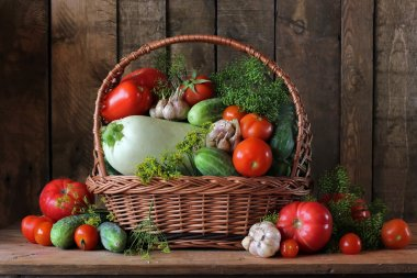 Basket with a vegetable marrow, cucumbers and tomatoes.