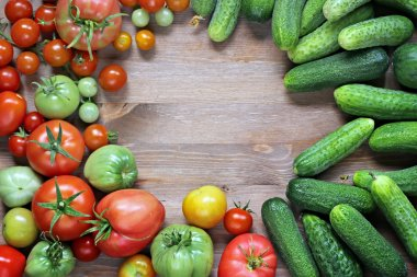 Fresh cucumbers, red and green tomatoes on a table