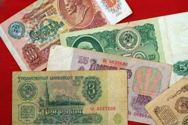 Old Soviet Russian banknotes: 1, 3, 10, 25, 50 rubles on a red b
