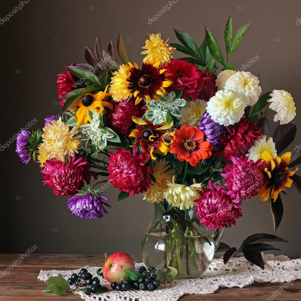 Still life with autumn flowers, apple and berries