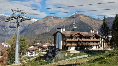 Mountain resort Krasnaya Polyana, the cable car, cottages and hotels, high mountains, snowy peaks and clouds