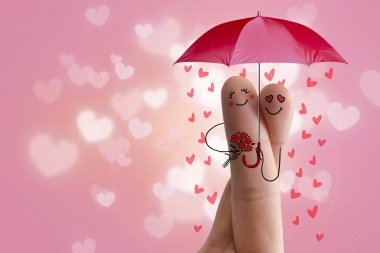 Conceptual finger art. Lovers is embracing and holding red umbrella with falling hearts. Stock Image