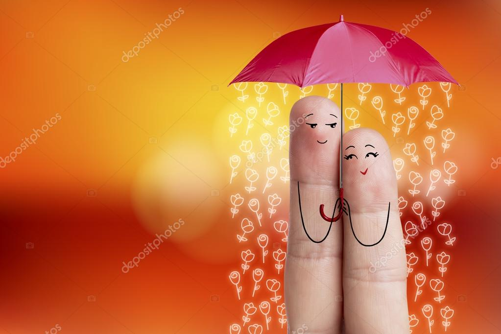 Conceptual finger art. Lovers is embracing and holding red umbrella with falling flowers. Stock Image