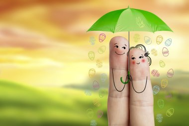 Conceptual easter finger art. Couple is  holding green umbrella with falling eggs. Stock Image