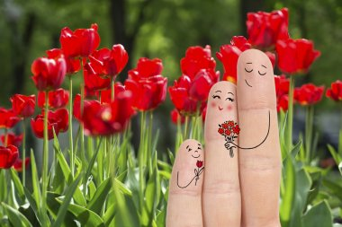 Conceptual family finger art. Father and son are giving flowers his mother. Stock Image.