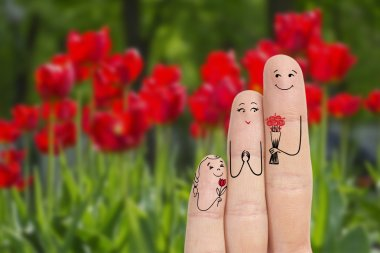 Conceptual family finger art. Father and daughter are giving flowers his mother. Stock Image.