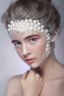 Beautiful girl with amazing make up and pearls and pink eye-shadows.