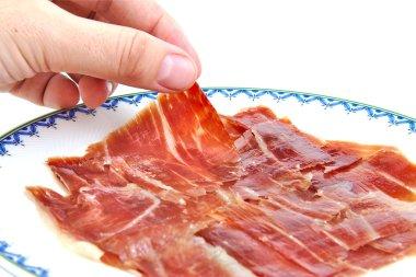 Mans hand holding an spanish serrano ham slice.