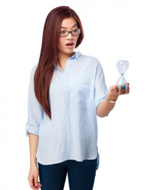 worried chinese woman with sand timer