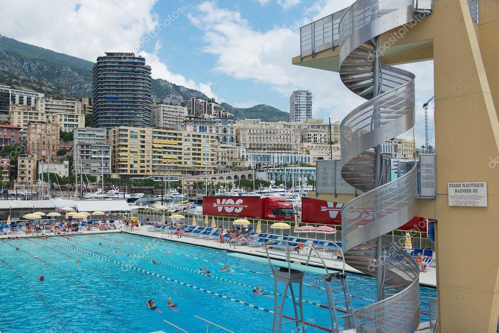 People Swim And Sunbathe At The Open Air Public Swimming Pool In Monaco Stock