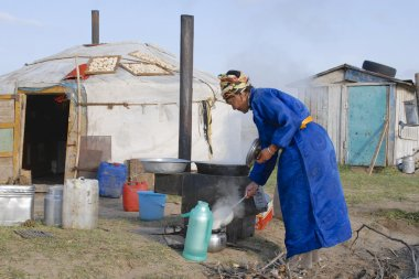 Woman cooks in front of the yurt in steppe, Mongolia.