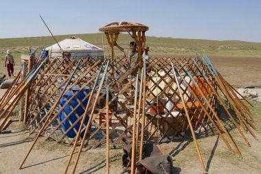 Mongolians assemble yurt (ger or nomadic tent) in steppe circa Harhorin, Mongolia.