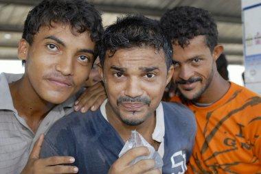 Fishermen drink water from transparent plastic bag in Al Hudaydah, Yemen.