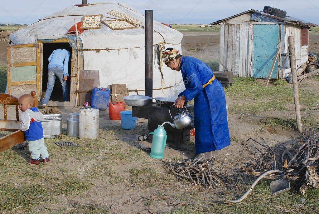 Women cook in front of the yurt entrance circa Harhorin, Mongolia.