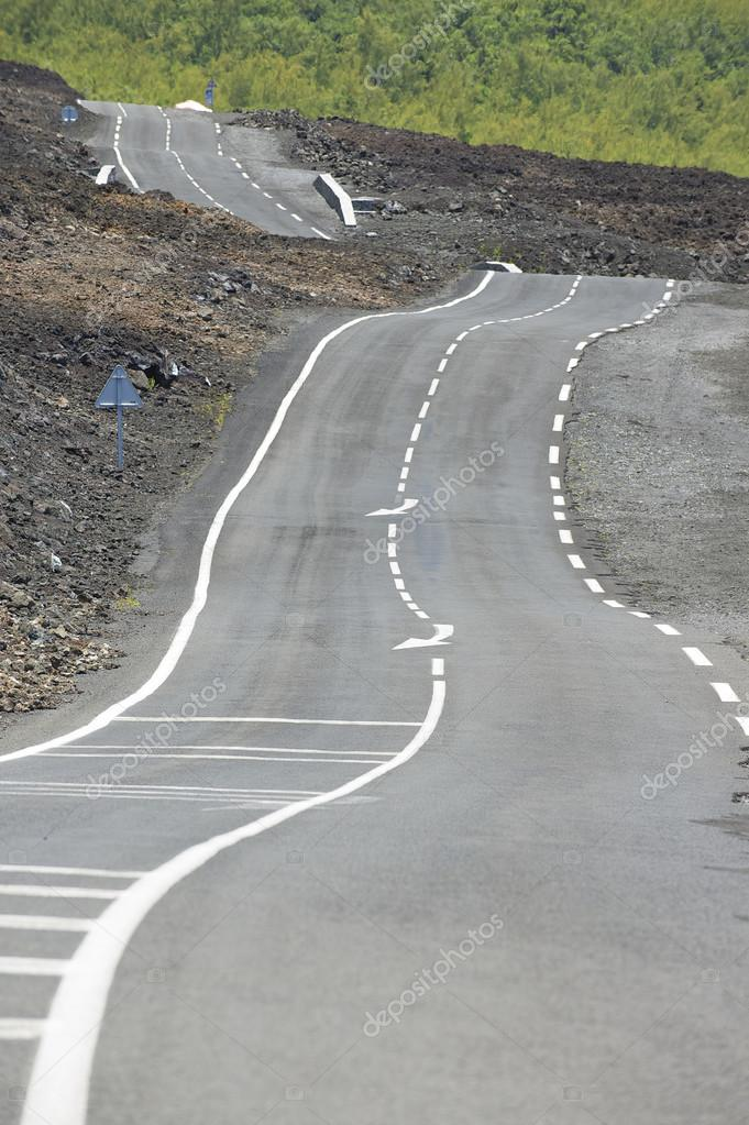 Curved asphalt road over volcanic lava, Reunion island, France.