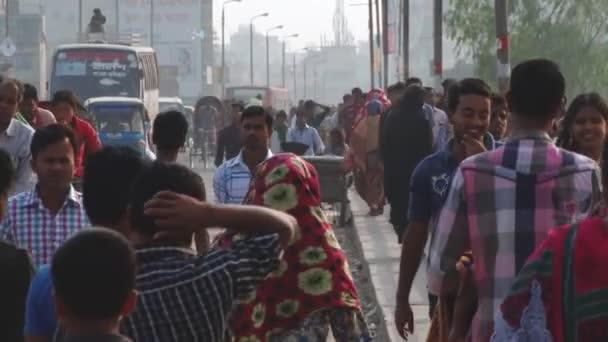 People walk by the street in Dhaka, Bangladesh.
