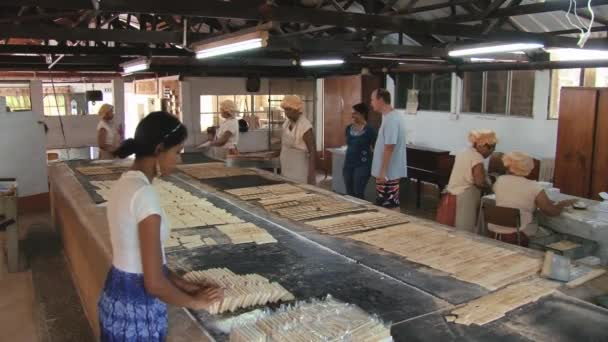 Women cook cassava biscuits at the famous Biscuiterie Rault in Mahebourg,  Mauritius