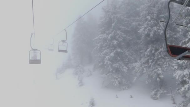 The seats of chair lift in the fog. Ski resort in the mountains ...