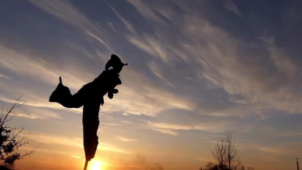 Stilt Walker Jumping on One Leg and Juggle. Slow Motion at Sunset.