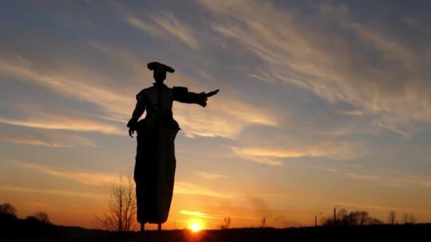 Stelzenläufer bei Sonnenuntergang winkt mit der Hand in die Sonne.