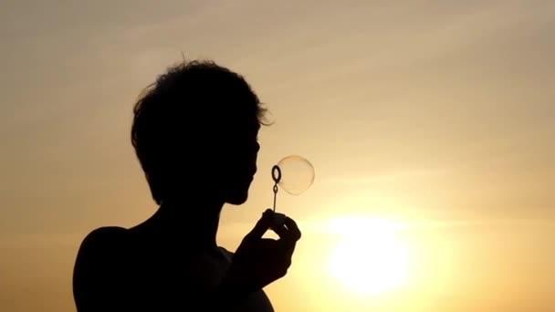Silueta muže foukat bubliny při západu slunce. Krásná akce v pomalém pohybu