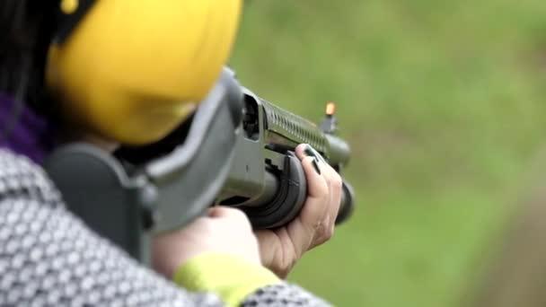 Lány spárgasípok egy vadászpuska közelről. Lassú mozgás.