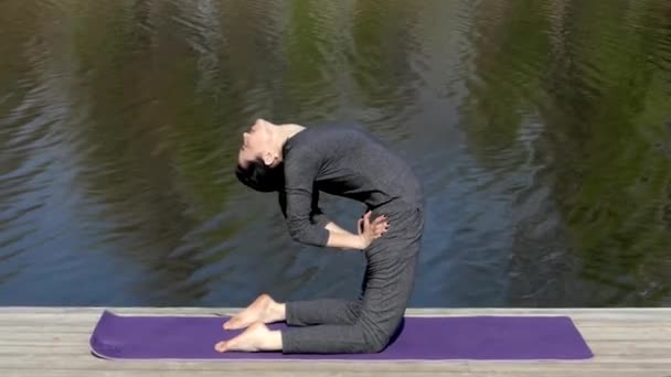 Yoga Teacher Make Camle Pose Near Water.