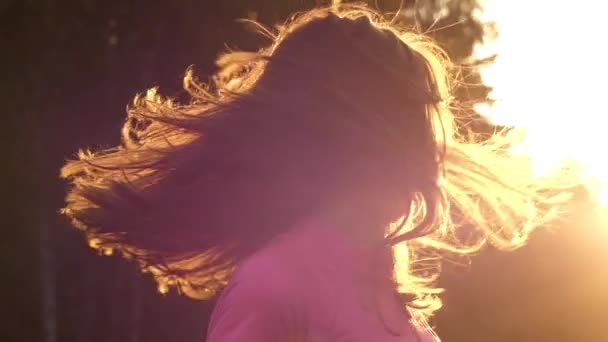 a Young Girl in Slow Motion Shake Her Head and Playing With Hair. the Action Takes Place at Sunset.