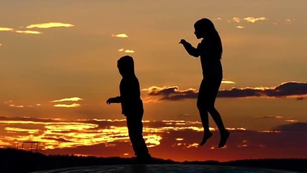 Kinder springen auf einem Trampolin bei Sonnenuntergang in Zeitlupe