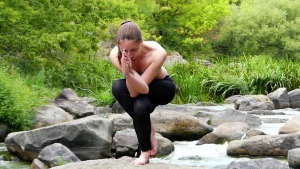 Hihetetlen mérleg egyik lábát egy jóga póz. egy lány áll, egy szikla közepén, egy hegyi folyó