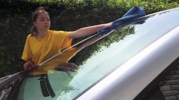 Mädchen bereinigen Sie ihr Silber Auto. Windschutzscheibe